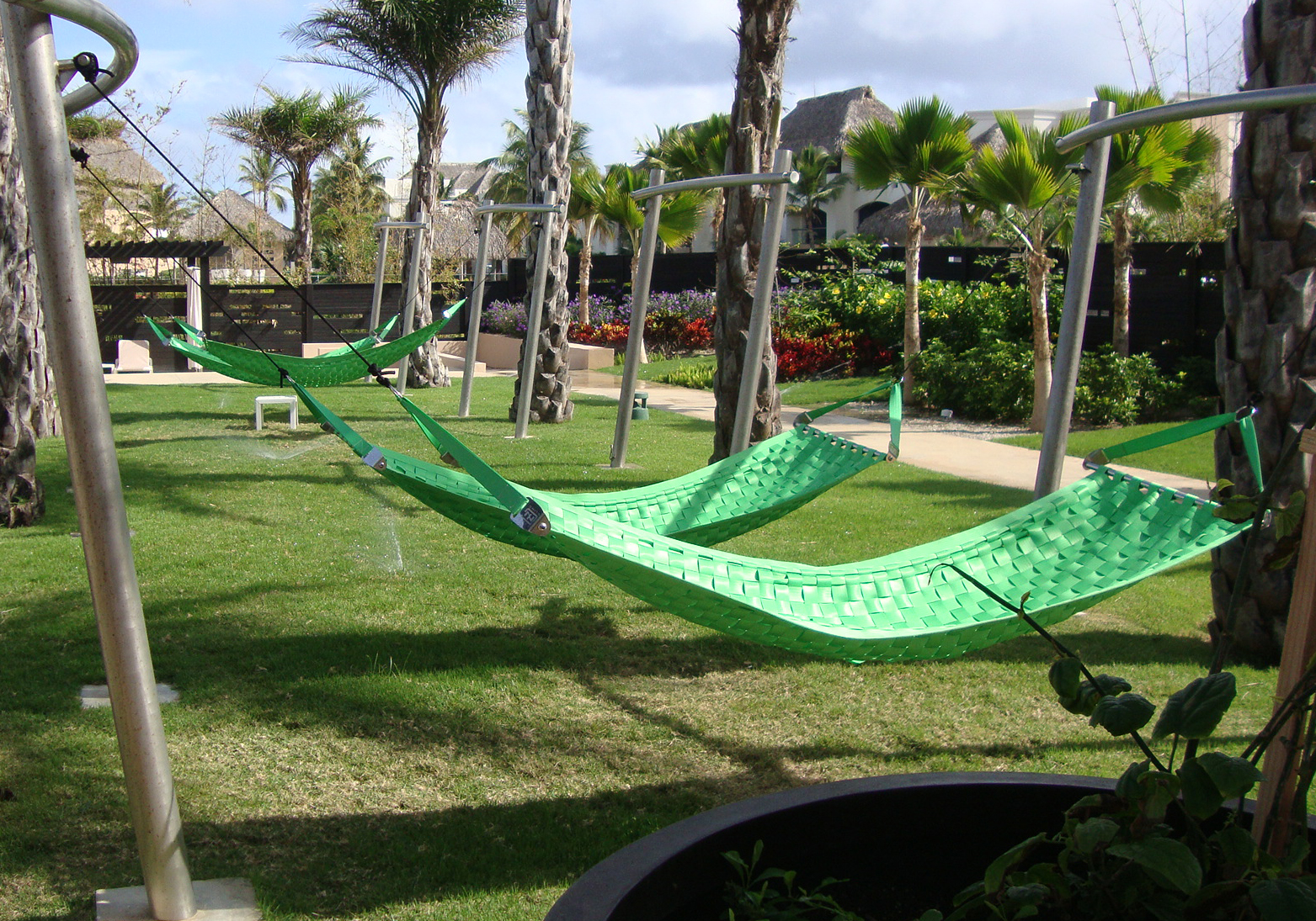 Four lime green Ting Sling seatbelt hammocks in a communal outdoor environment.