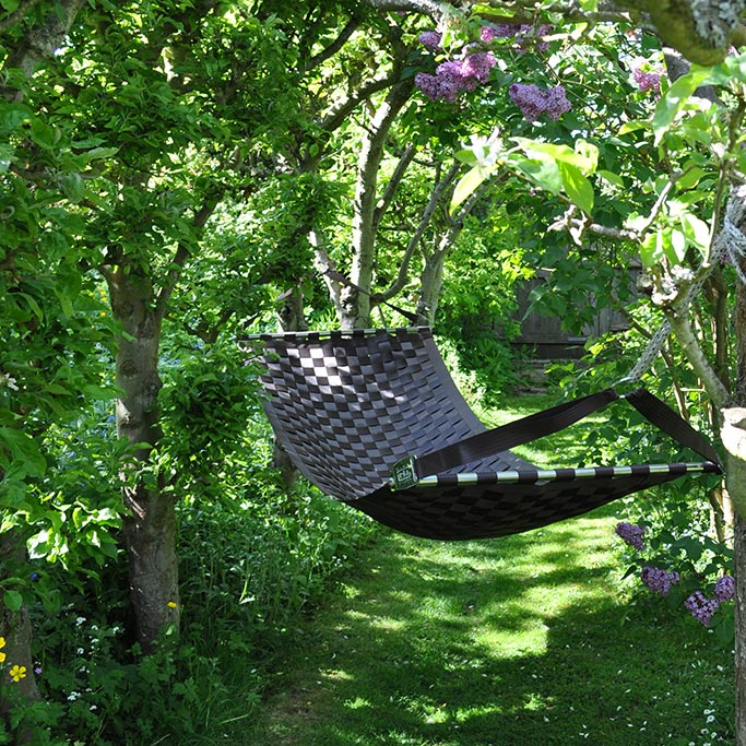 Black Ting Sling seatbelt hammock hanging among trees and greenery in a private garden in the idyllic English countryside.