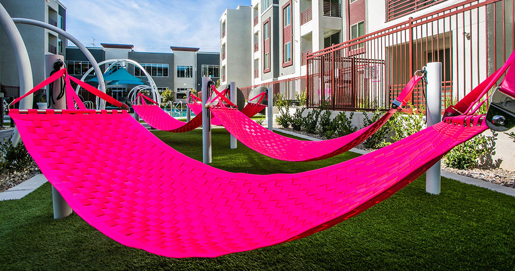 Several Ting Sling seatbelt hammocks, as seen in the pool area of a luxury apartment complex.