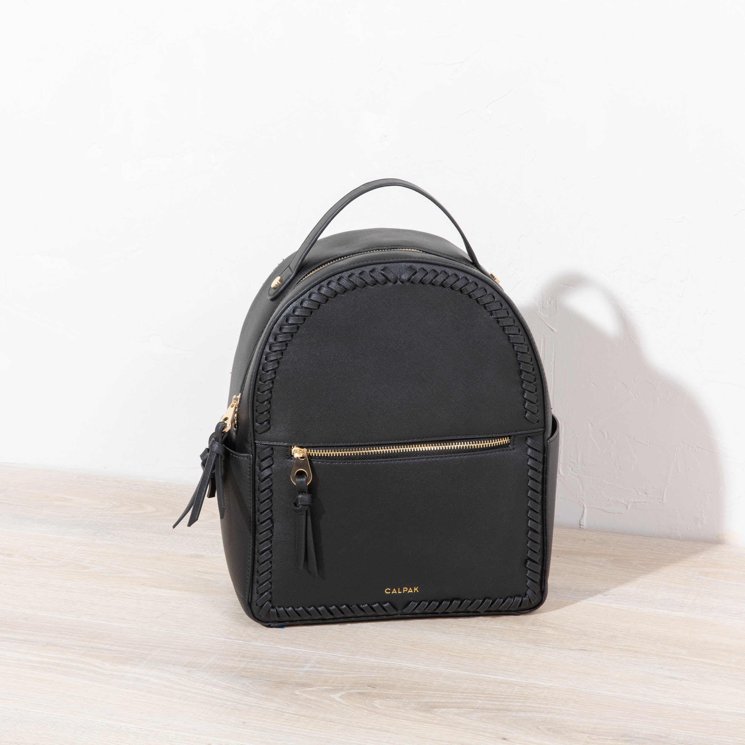 "Kaya Backpack - Black - We like to think of this backpack as the ""I'm going places,"" backpack. The Kaya backpack is perfect for all the times you have too much stuff for a purse, and too little for rolling luggage. Your water bottle, your ipad, your mid-day snack, your headphones, and more, will all fit neatly and sweetly in this travel BFF."
