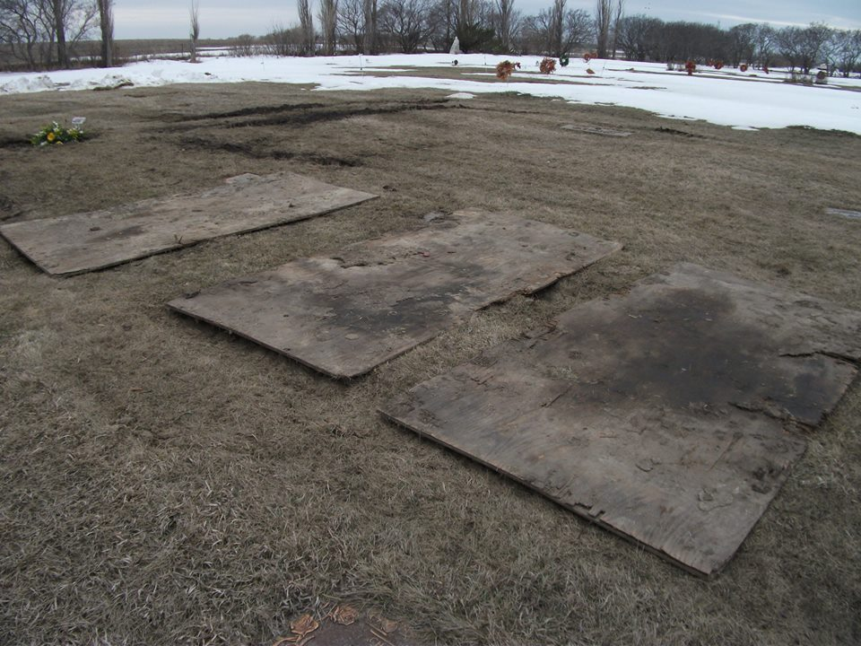 Broken plywood planks, ruts in turf, brown wreaths in background