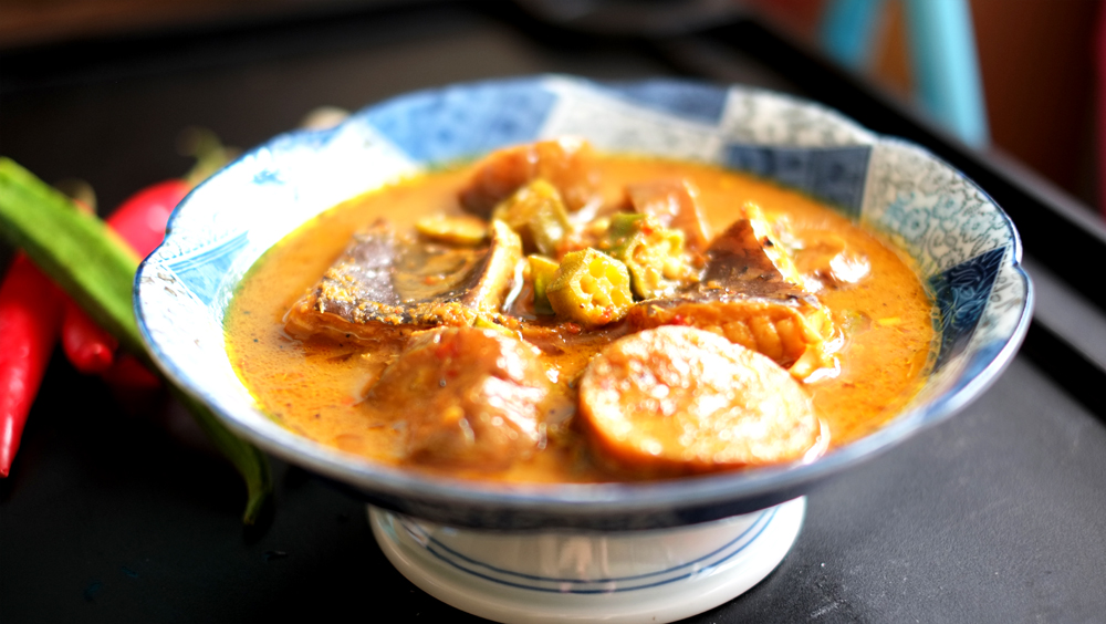 Nyonya Kuah Lada   Prep time: 20 mins  Cook time: 30 mins  Total time: 50 mins  Serves: 6     Ingredients:   · 2 medium-sized pieces of Stingray/Skate (cut into chunks)  · 1 eggplant  · 6 strips of Okra  · 2 strips of Lemongrass  · 3/4 cup of Tamarind flesh/pulp   For the paste or Rempah   · 15 Shallots (peeled)  · 1 small piece of Blue Ginger  · 2 small pieces of Yellow Ginger    Instructions:  1) First, prepare the paste (or Rempah) by roughly cutting up the chillies, blue  ginger and yellow ginger into smaller pieces, and tossing these into a  blender with the shallots, pepper seeds and shrimp paste. Blend it until you  get a paste-like consistency.  2) Set the Rempah aside, we will only need it after the other ingredients are all  prepared.  3) Next, pound the lemongrass stalks. It would be best if you had a mortar and  pestle you could work in, but if you don't have one of those in the kitchen,  simply pounding with the back of your knife works fine as well.  4) Time now to work on the Tamarind/Assam water, squeeze the tamarind  pulp over a bowl until the juices run, after which pour 2 cups of water in  with the juices and mix. Set this aside.  5) Grab the eggplant and Okra and start slicing them up.  6) Rub salt over the stingray pieces, and set them aside.  7) Heat up 2 tablespoons of vegetable oil in a wok until hot.  8) Gently spoon in the paste and stir it around in the oil until it is fragrant  (about 2-3 minutes).  9) Next, throw in the stingray, eggplant and okra and give it a good toss-about  until they are all generously coated with the paste.  10) Add in your Tamarind water and when it comes to a boil, lower the fire and  allow to simmer until the eggplant and okra are soft, and the stingray is  cooked through.  11) Taste the gravy, and add sugar to balance out the sourness of it (roughly  about 1-1 1/2 tablespoons). Remember, DO NOT ADD SALT!  12) Serve the Kuah Lada with jasmine rice.