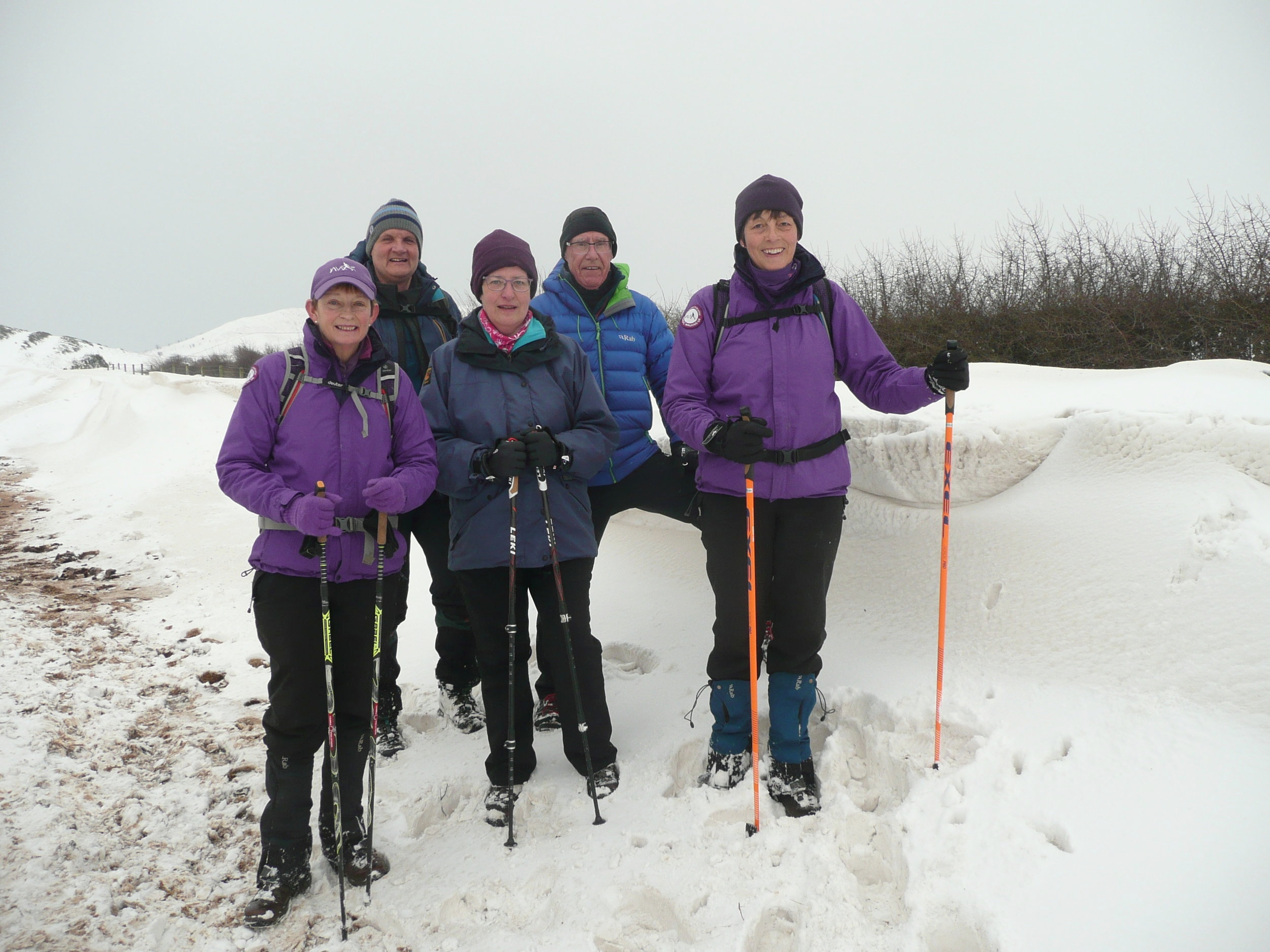 Two female Nordic Walking instructors wearing purple jackets, holding nordic walking poles leading two males and one female in deep snow on North York Moors