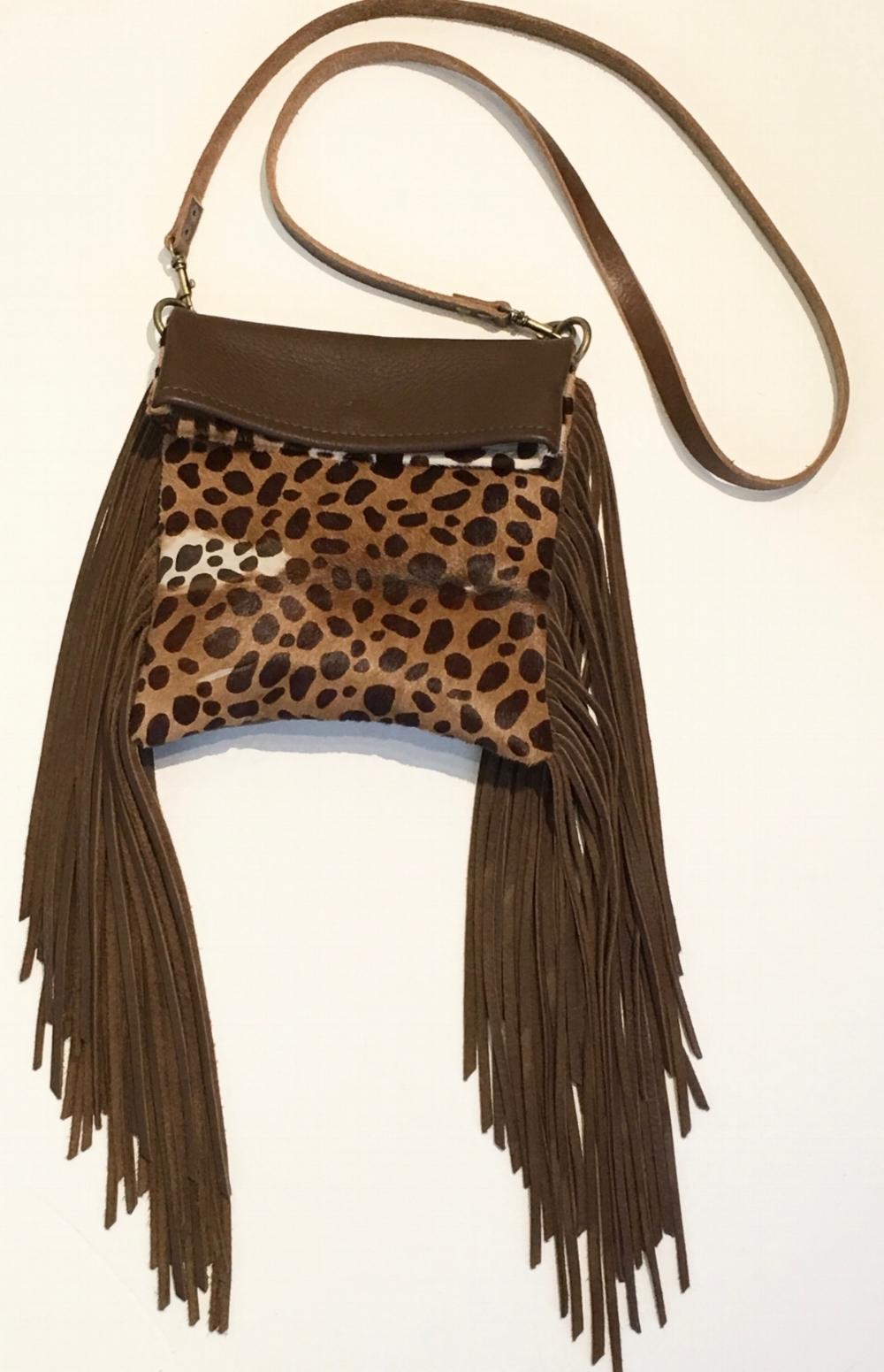 Reversible one side soft brown deerskin, the other hair on hide Handbag with long strap.  Lambskin fringe and magnet closure.  $380., .jpg