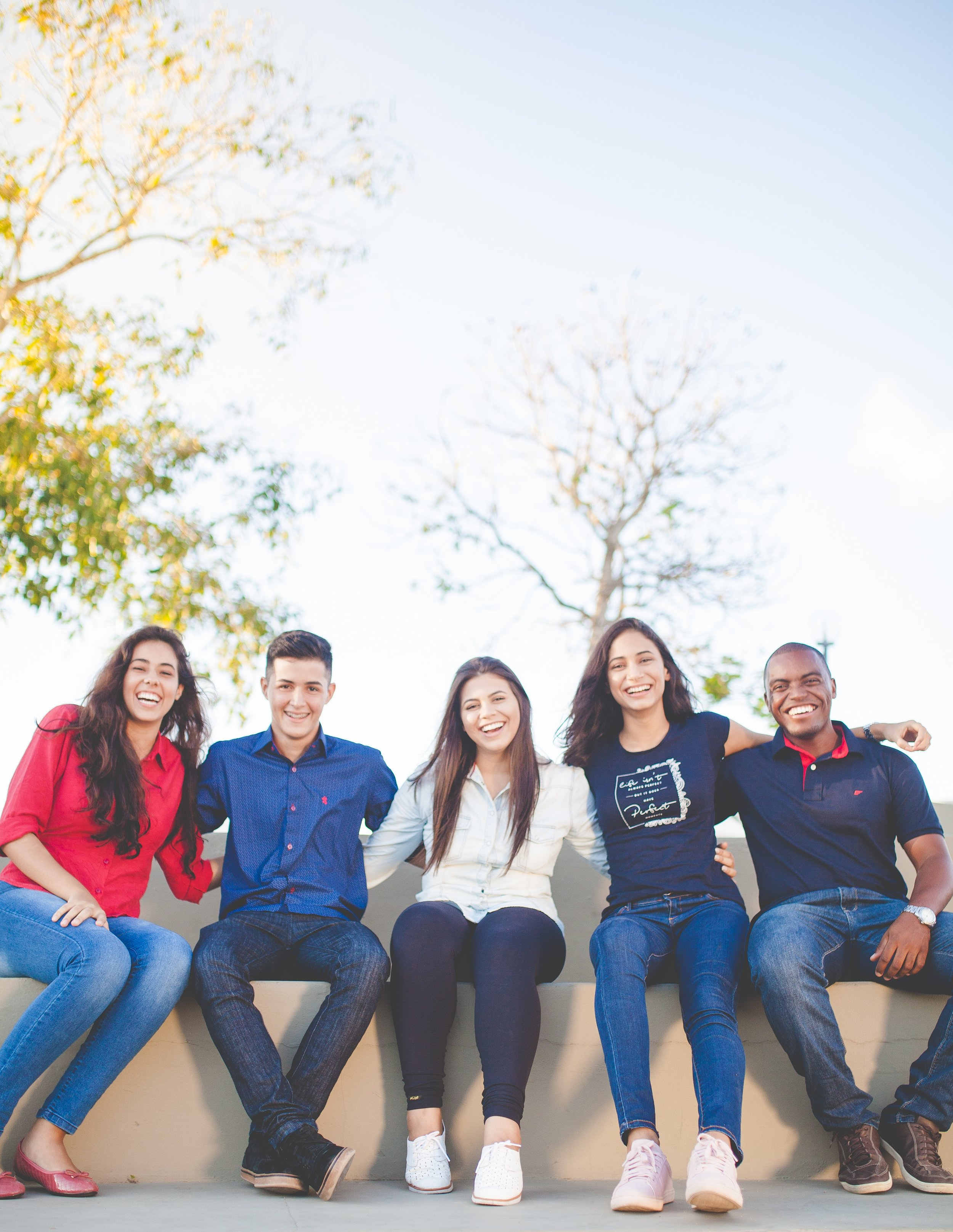 Five students sitting, smiling and posing for photo