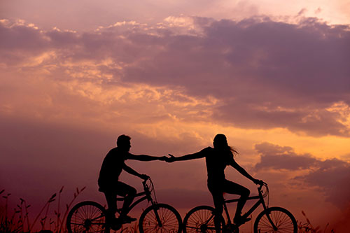 Silhouette of couple riding their bikes holding hands during sunset