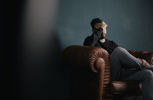 Man sitting on brown couch with hand on forehead looking worried and stressed