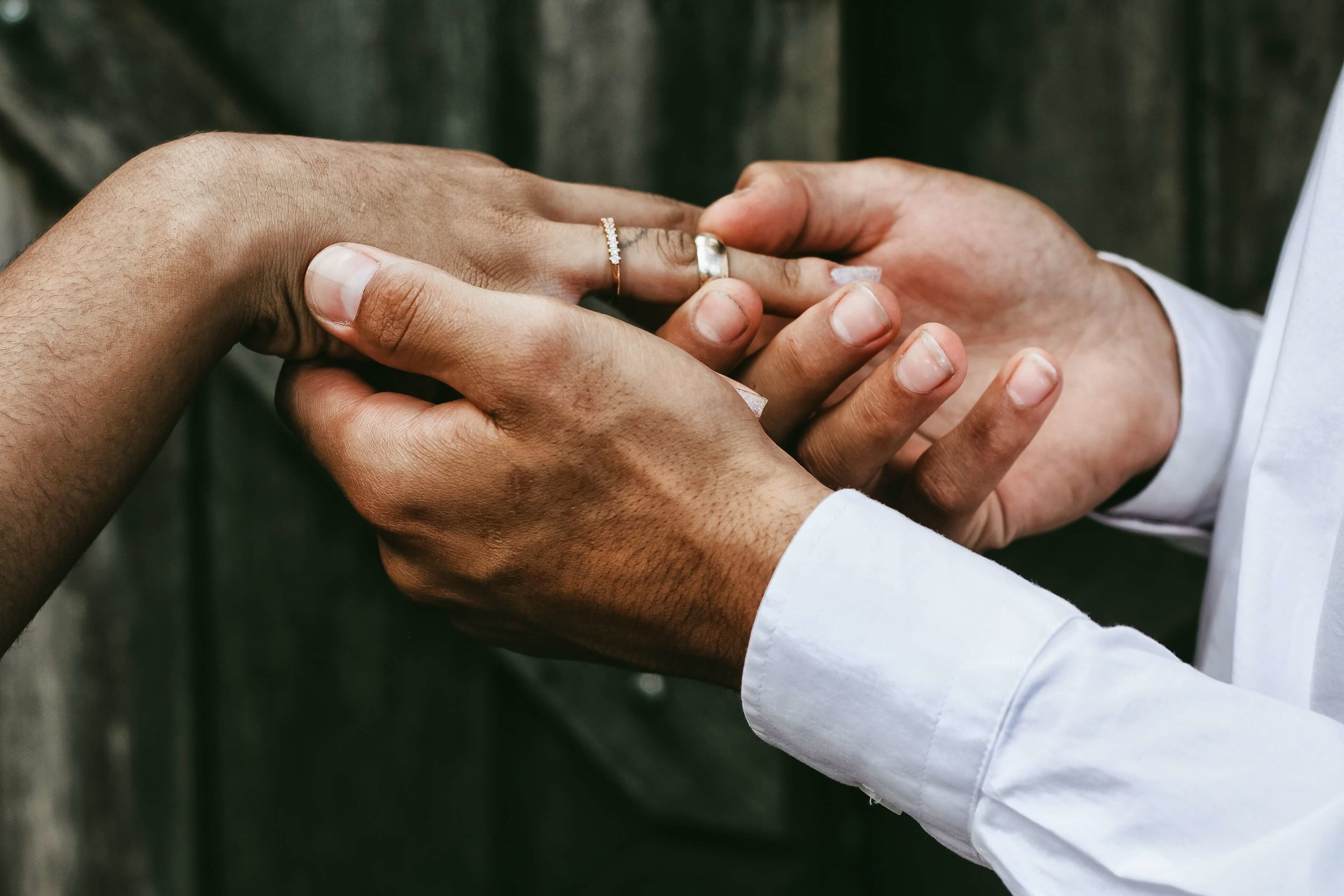 close up of hands exchanging rings