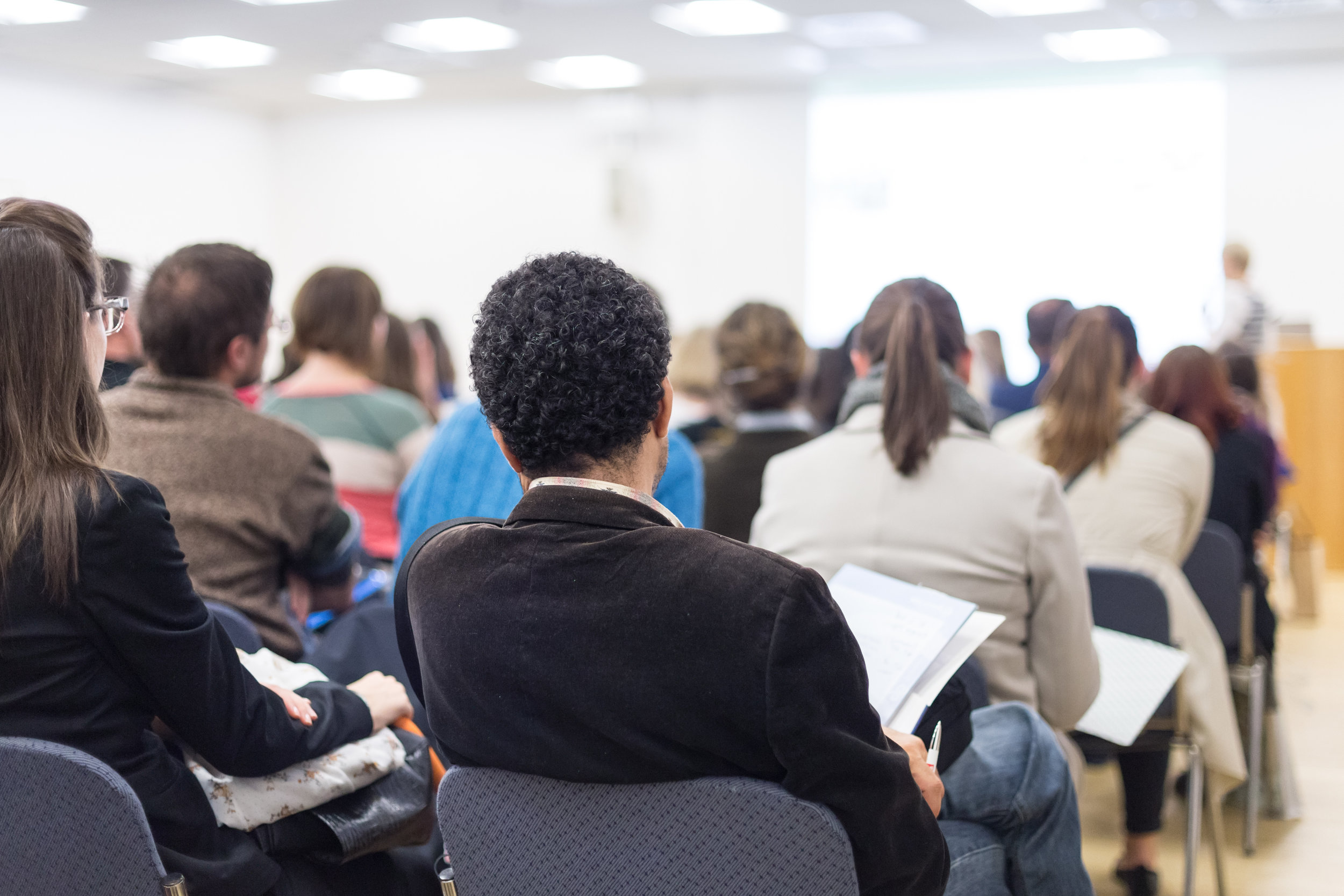 Professionals listen to a speech in a business environment