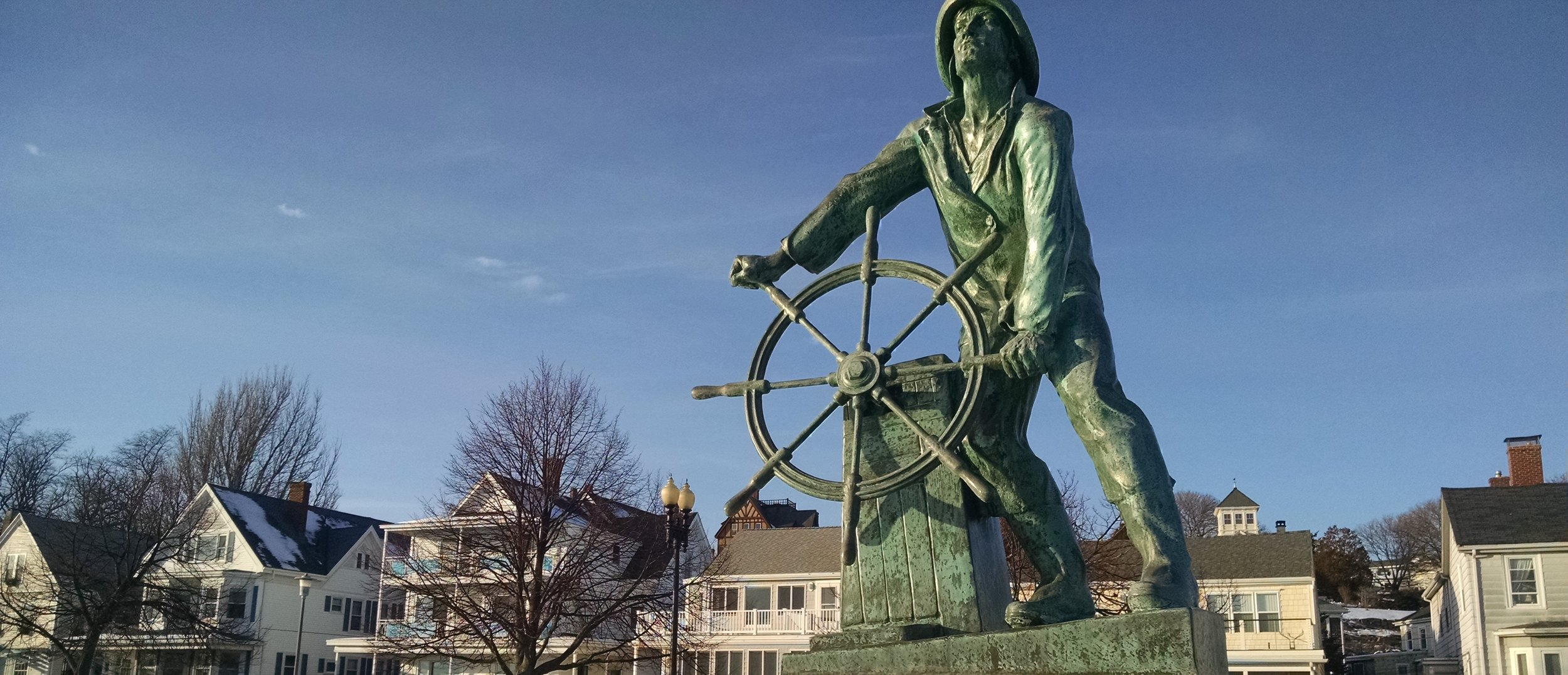 Image: A statue of a man in foul weather gear leaning into a ship's wheel and looking out into the distance. This status is in Gloucester, MA.
