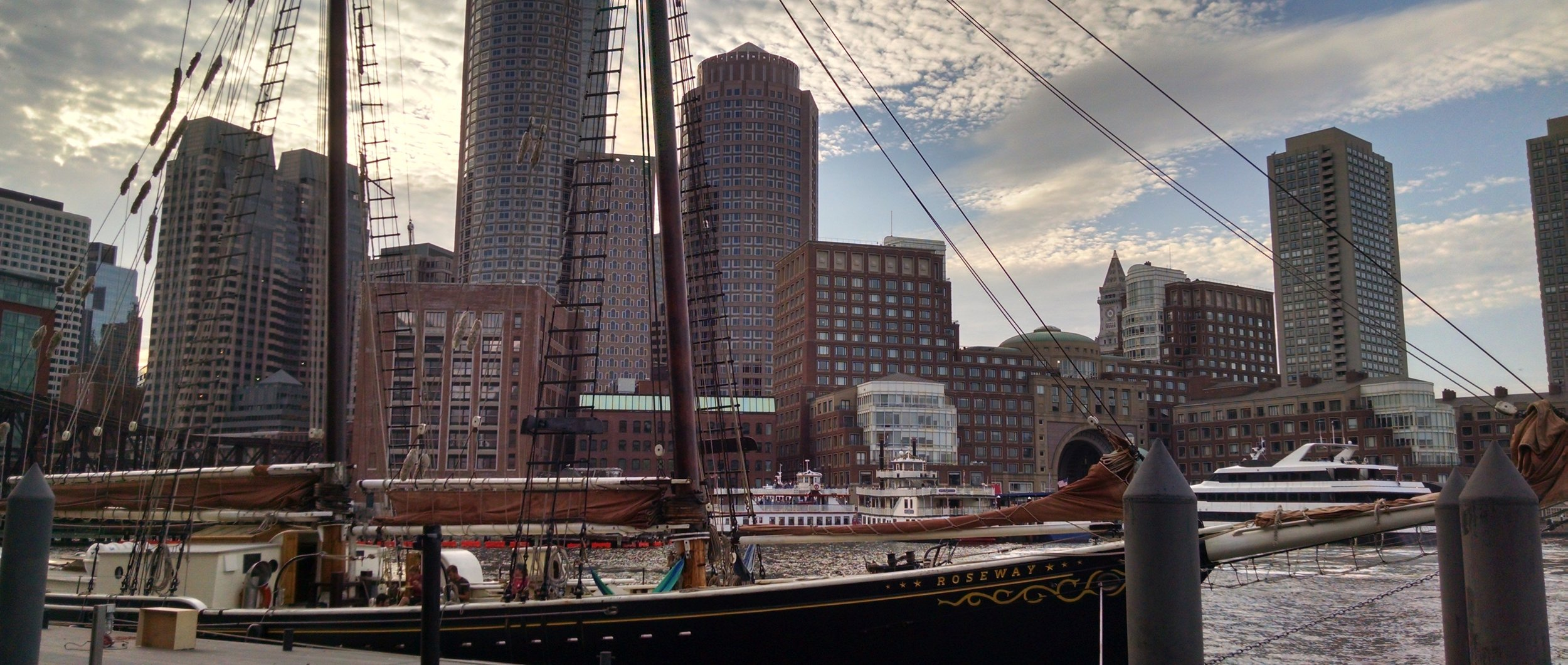 Image: The Boston Harbor and part of the skyline, with the tall ship Roseway in the foreground and modern yachts visible in the background.