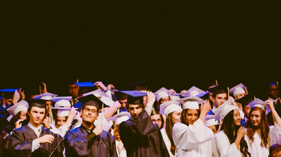 Image: Rows of young people wear graduation caps and gowns. Author: StockSnap. Source: https://pixabay.com/en/people-men-women-graduation-school-2562626/