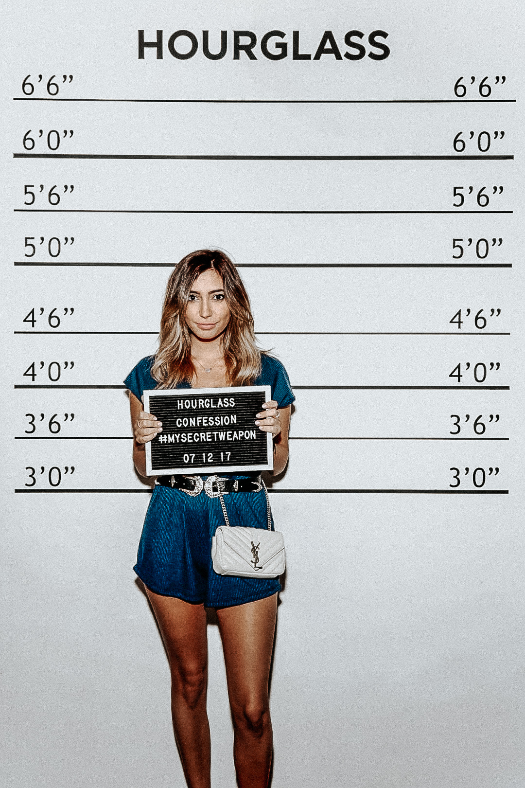 My MUGSHOT. Iconic! - WE WORKED OUR WAY THROUGH THE ROOMS BACKWARDS… THIS WAS DEFINITELY SUPPOSED TO BE THE FINALE BUT OH WELL!I gotta admit… I'm not as tall as it says in my mugshot. Thank you to my chunky heels that gave me an extra couple inches in this shot 😉 I'm actually just 5 feet… most people are pretty surprised by my size when they see me in person. I used to always wish I was taller, more like 5'4 or something like that… but anyways, we're getting off topic!Let's talk outfit details…Romper | Shoes (similar) | Belt | Purse