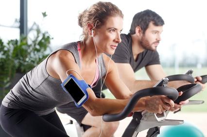 man_woman_exercise_bike_headphones.jpg