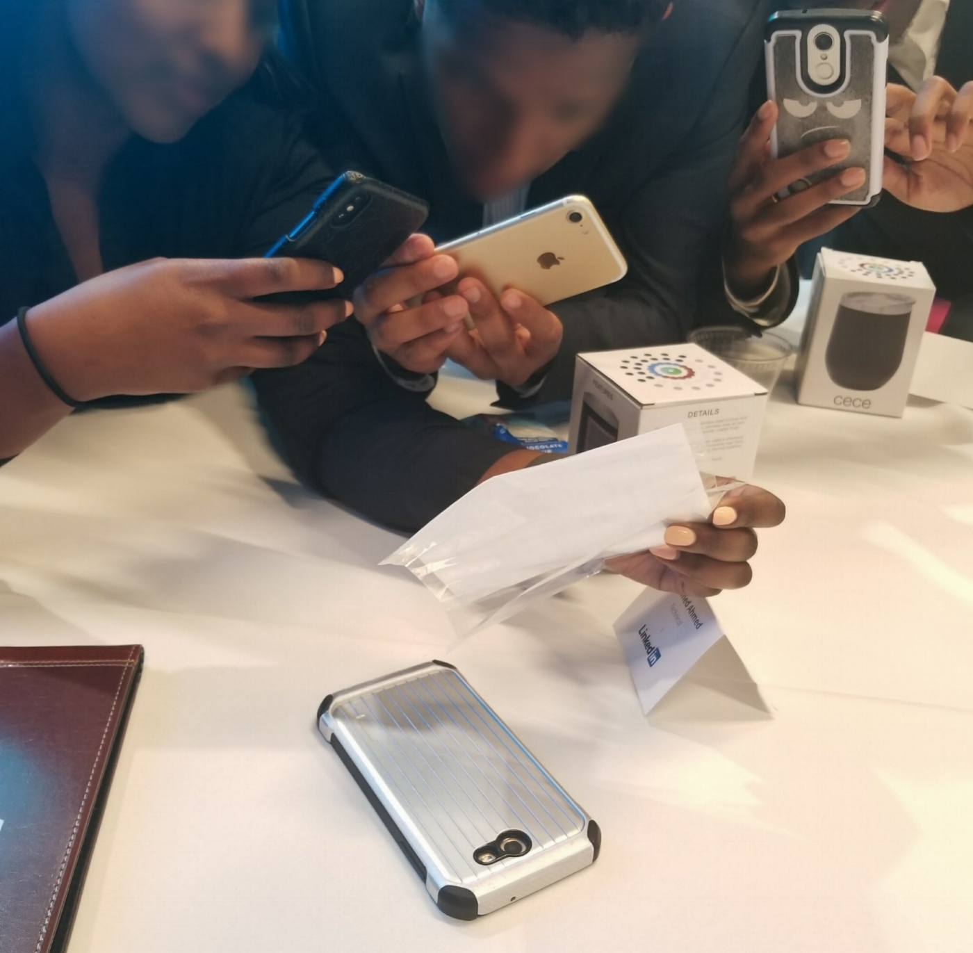 Members at a conference taking a picture of a name badge to then go back and search to connect. -