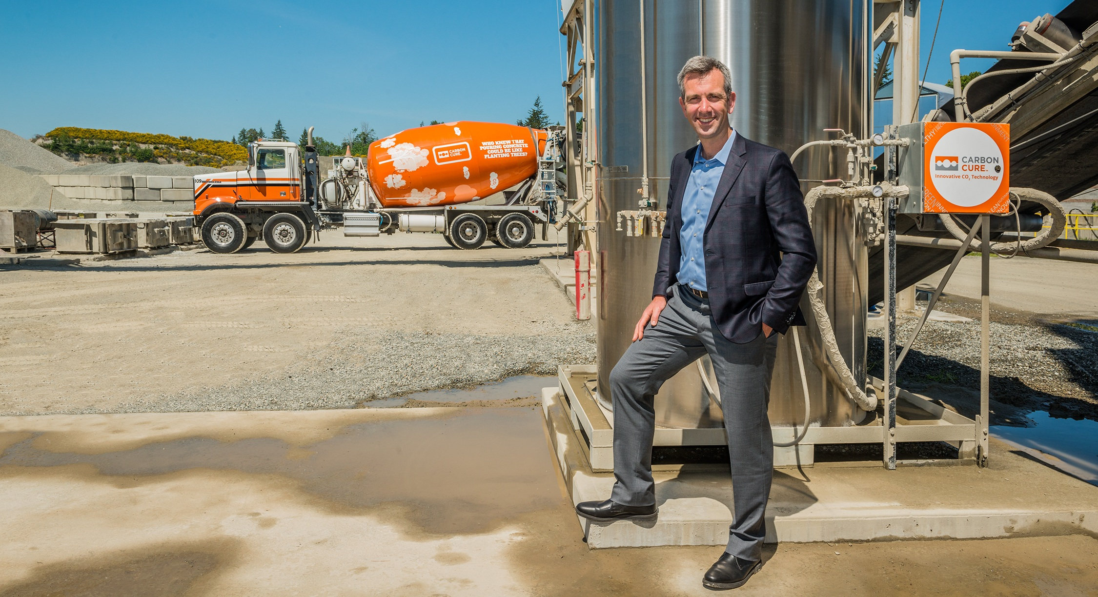 Rob Niven stands before a CarbonCure tank that stores carbon dioxide at a concrete plant.