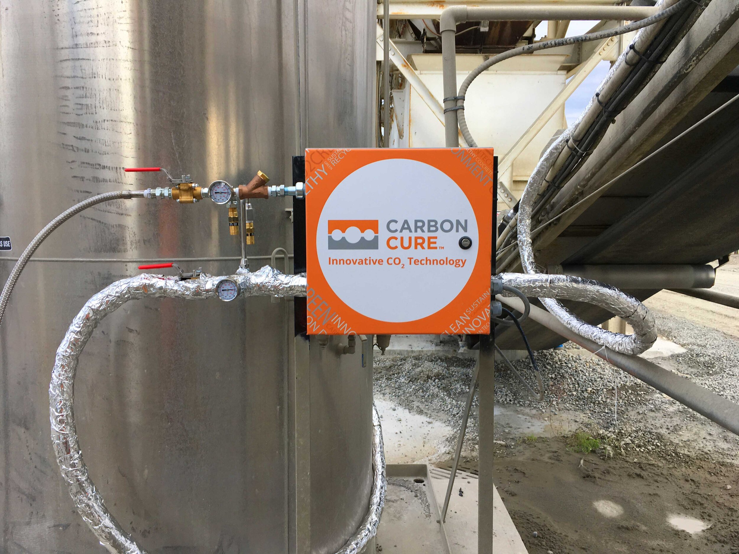 The CarbonCure valve box hooked up to the CO2 tank on one side and the injection nozzle on the other via insulated transfer hoses. The valve box is also connected to the control box by a control cable.