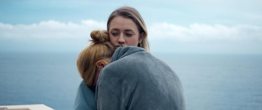Under bølgerne, over skyerne :  De to veninder, Helene og Theo, rejser til Kreta for at genforene Helene med en gammel ferieflamme. Livet er herligt, og alt kan ske. Men da planen kuldsejler, må de to unge kvinder kæmpe mod uventede, indre dæmoner.  Under Bølgerne, Over Skyerne  undersøger den hårfine grænse mellem galskab og genialitet, kontrol og afmagt. Samtidig er filmen en skildring af, hvor meget styrke der er at hente i venskaber. Foto: Mia Mai Dengsø Graabæk