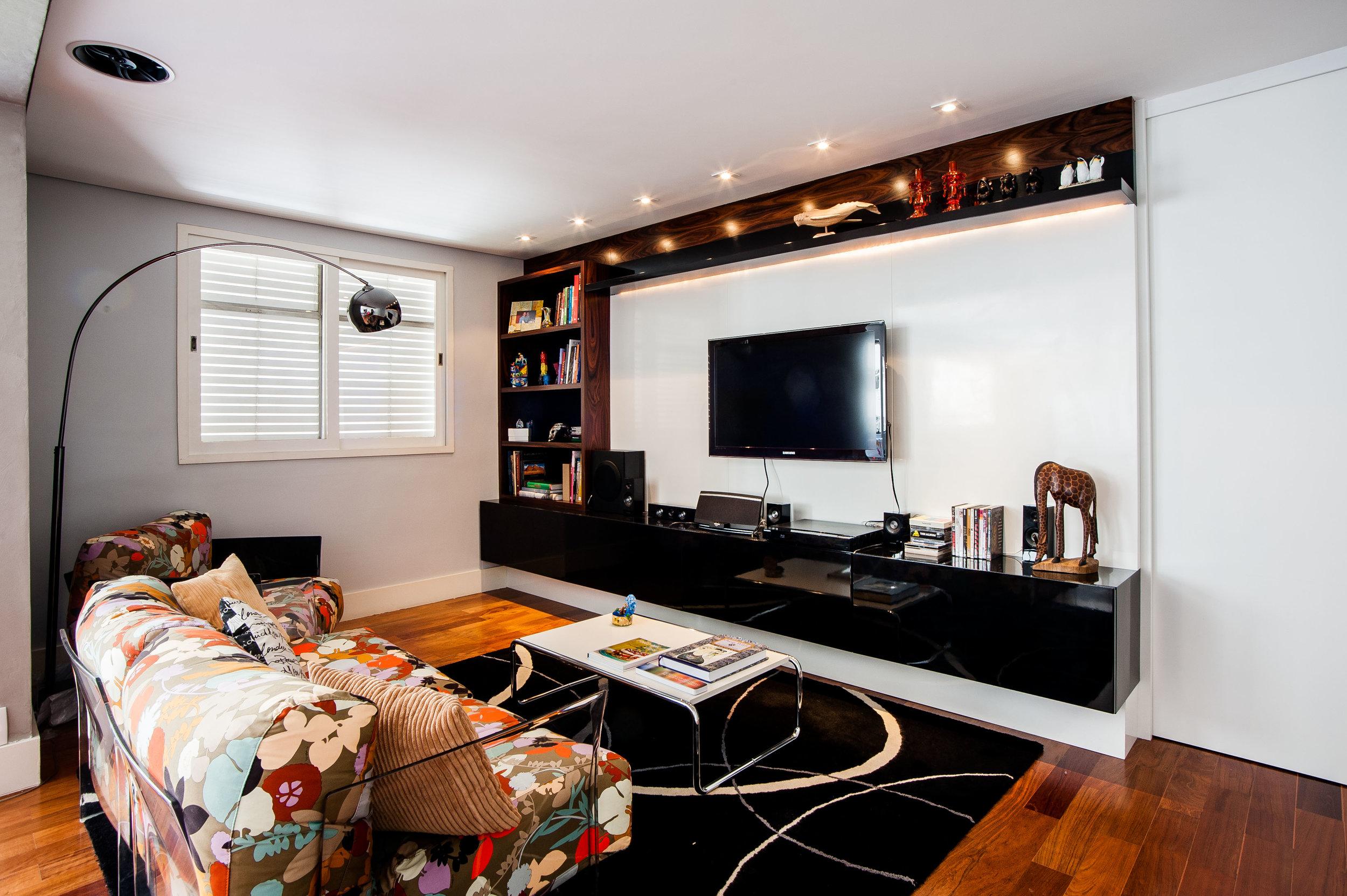 Na sala de estar o móvel projetado para a estante e televisão tem acabamento em madeira pau-ferro, laca preta e branca. O sofá da Kartell conta com tecidos da Missoni. O lavabo tem paredes e pisos em cimento queimado e bancada em mármore Nero Marquino.