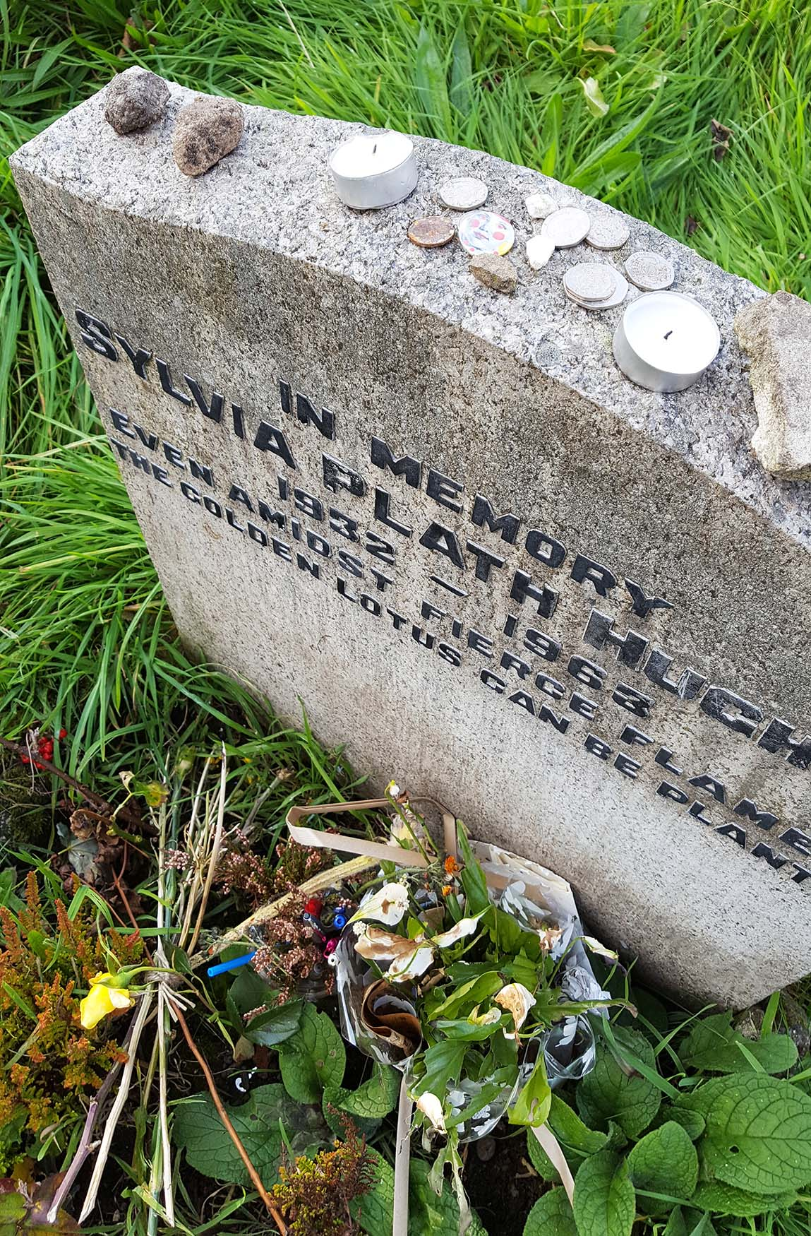 Pens, pennies, flowers and letters left at Sylvia Plath's grave