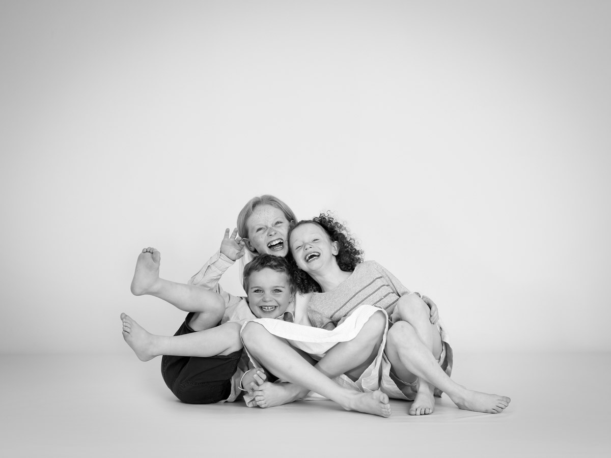 siblings falling over during their portrait