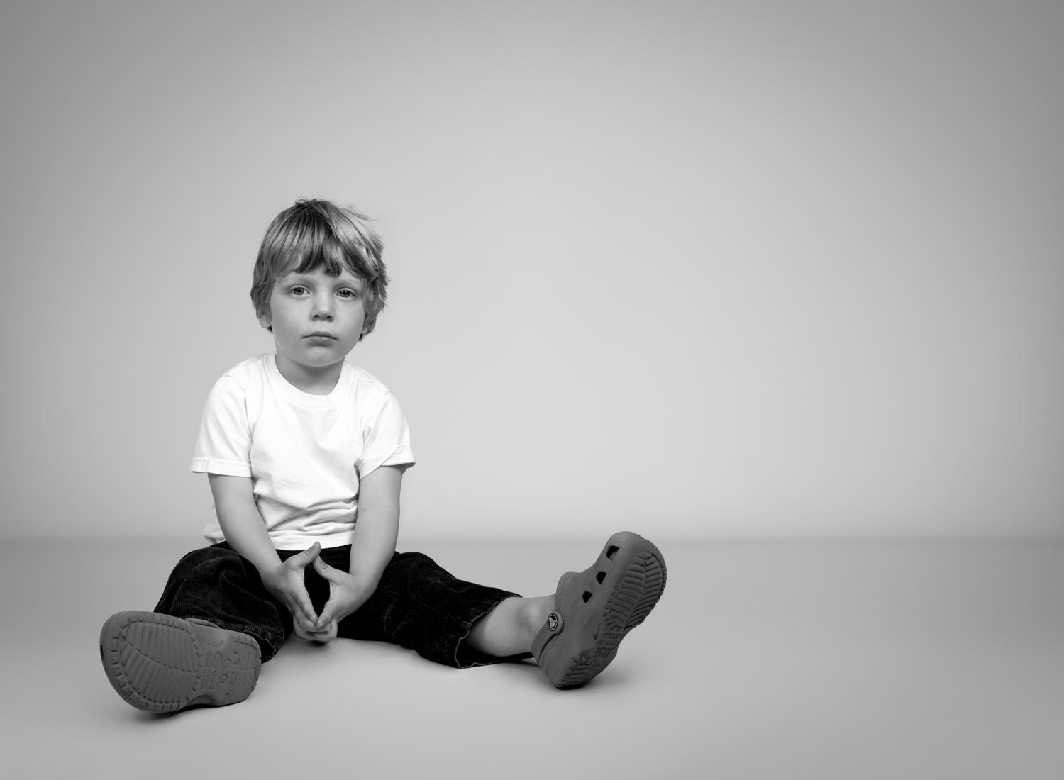 Black and white portrait of boy wearing crocs