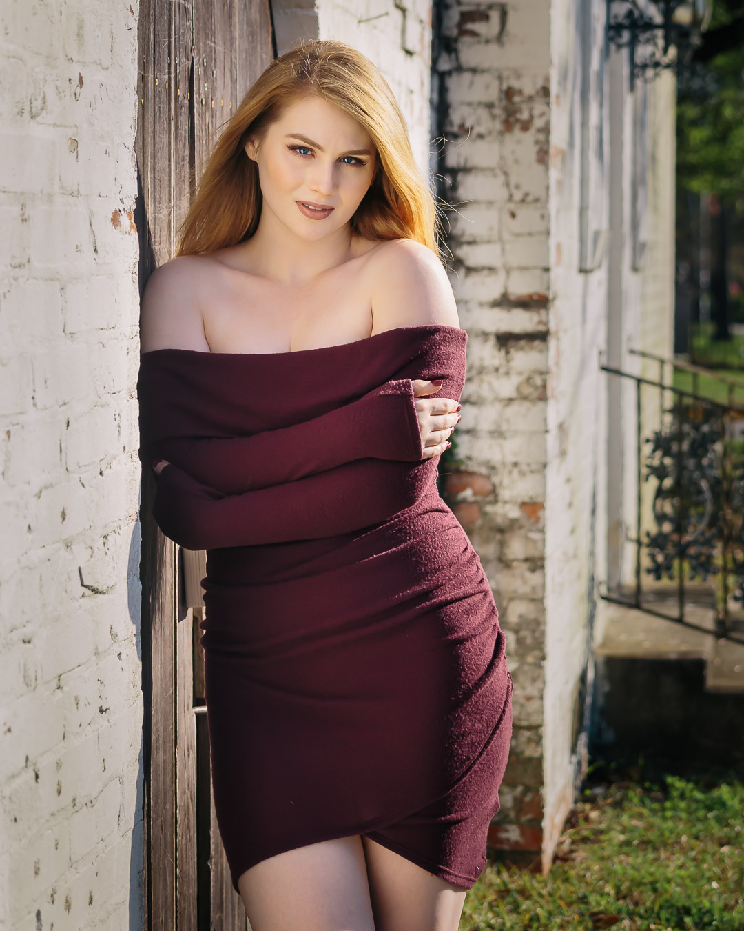 Senior girl in maroon dress off of shoulders in small town