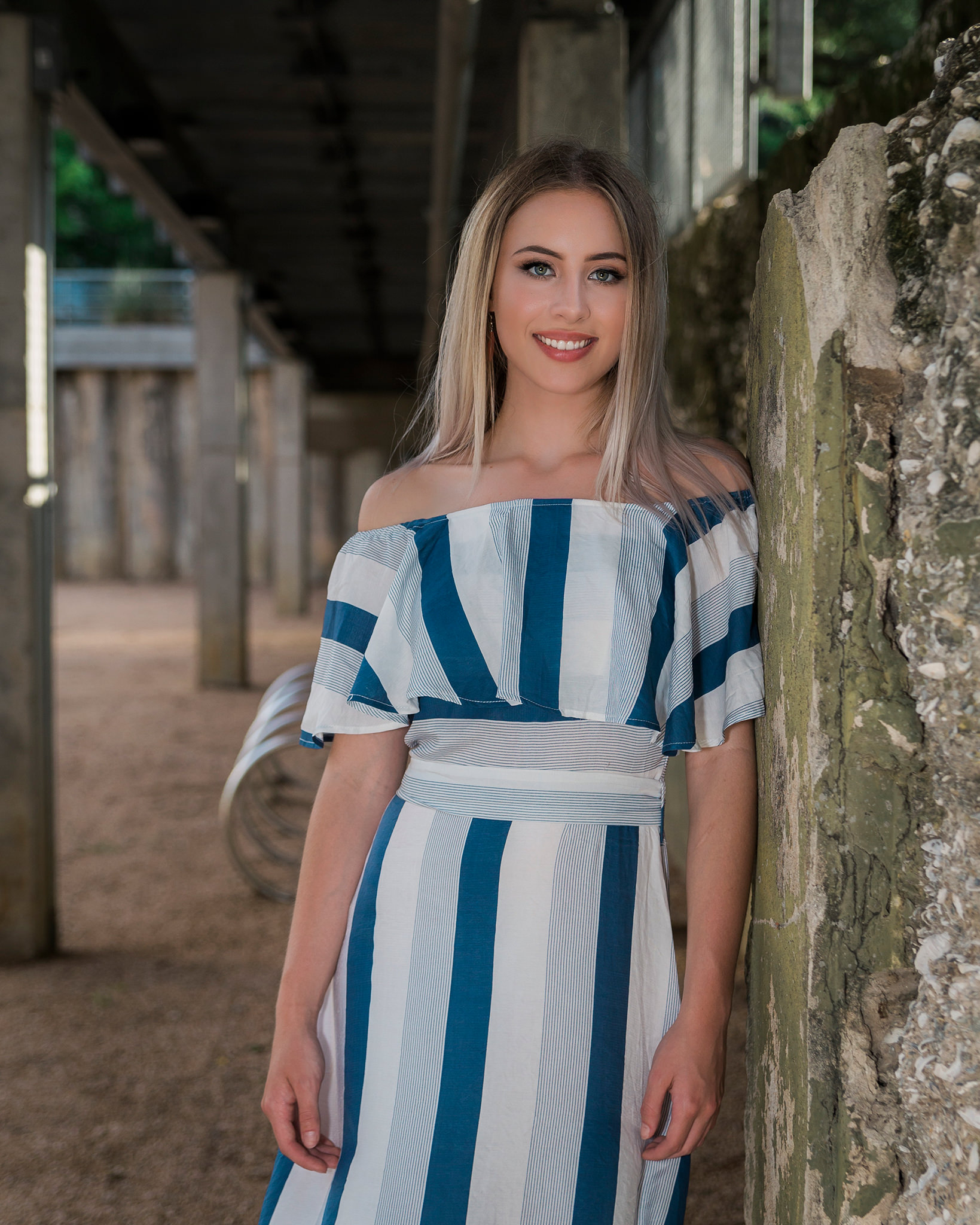 Senior girl against wall with white and blue striped dress