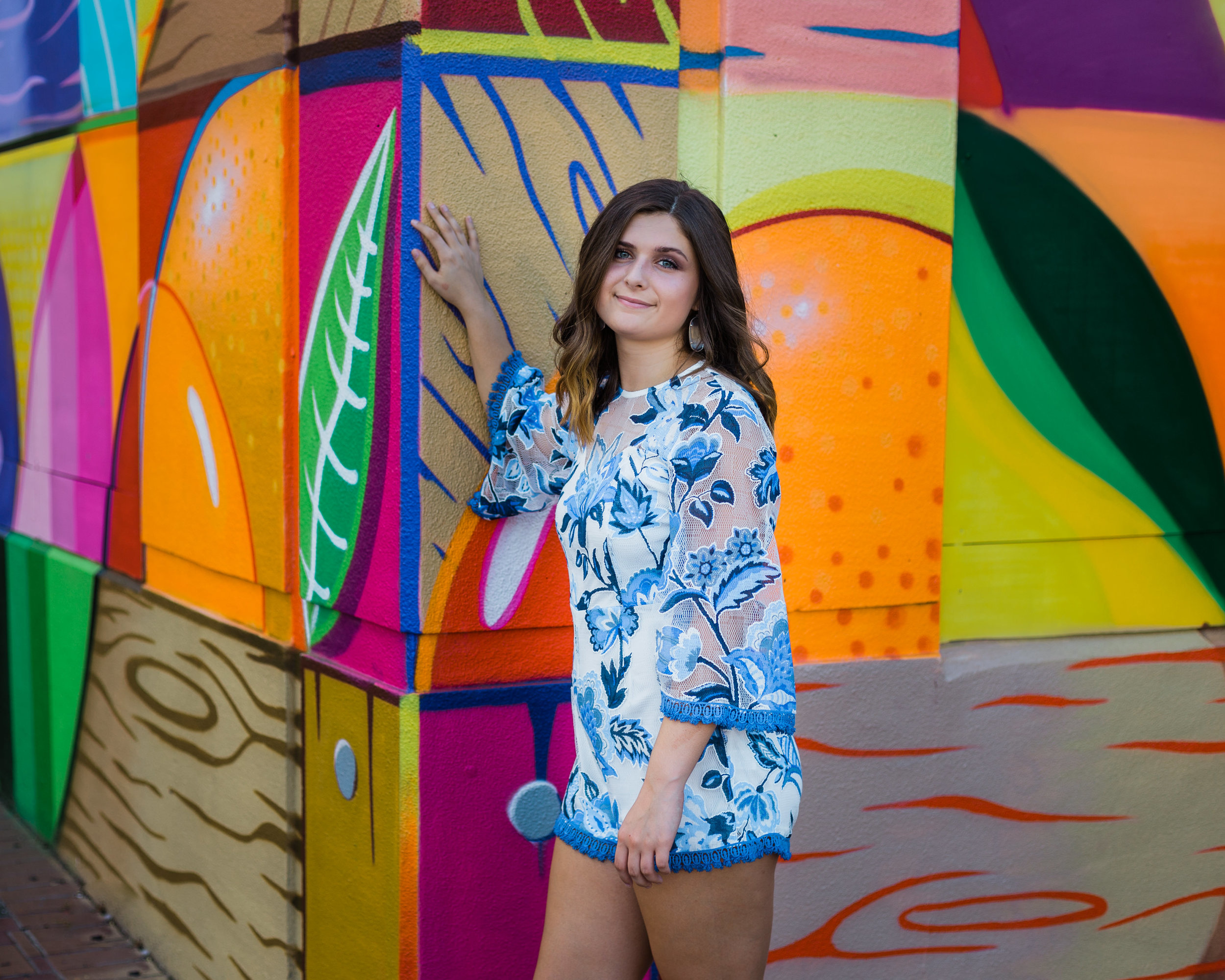 Senior girl in romper with bright urban painted wall