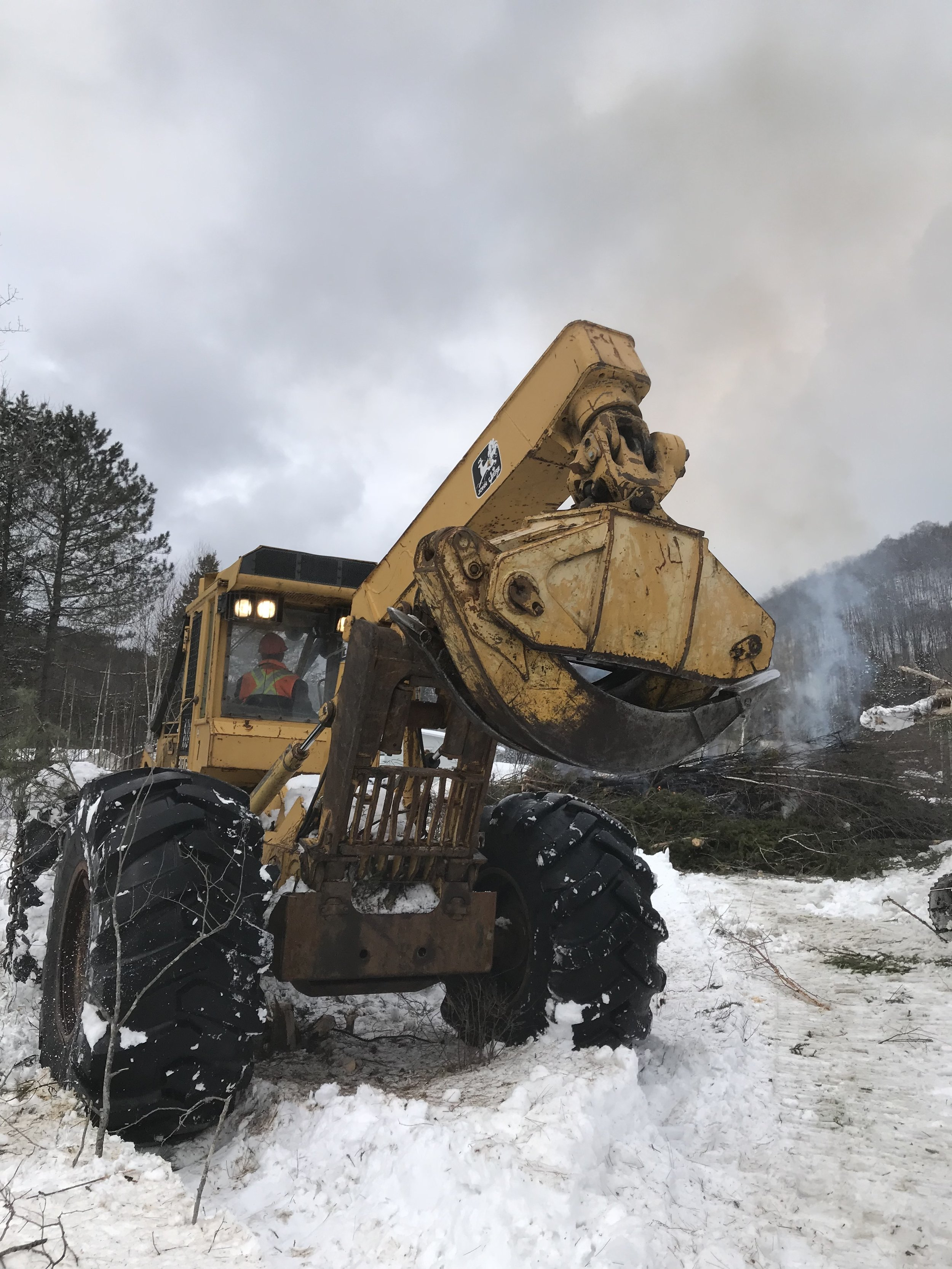 A variety of machinery and equipment is being utilized in the clearing of the site.
