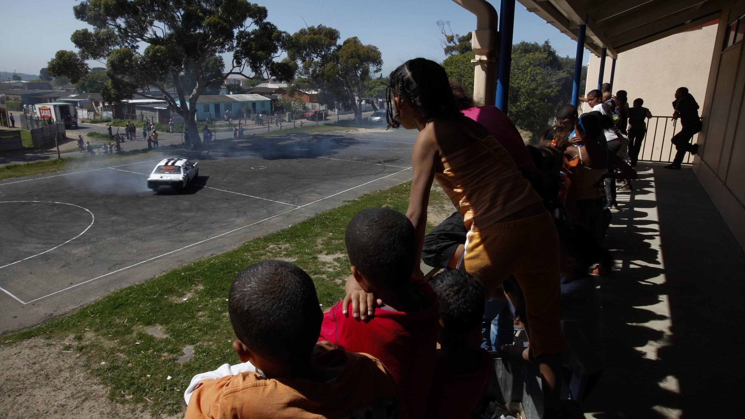 CHILDREN IN ELDORADO PARK WATCH A SPINNER. CREDIT: NIC BOTHMA/EPA/SHUTTERSTOCK