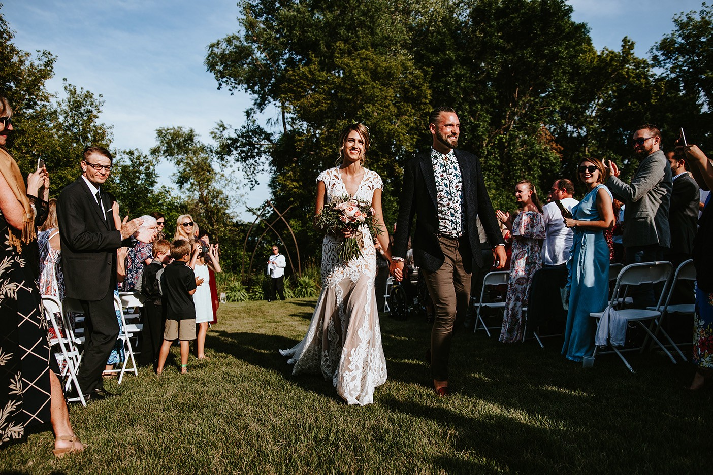 tris and dany walk down the grass aisle