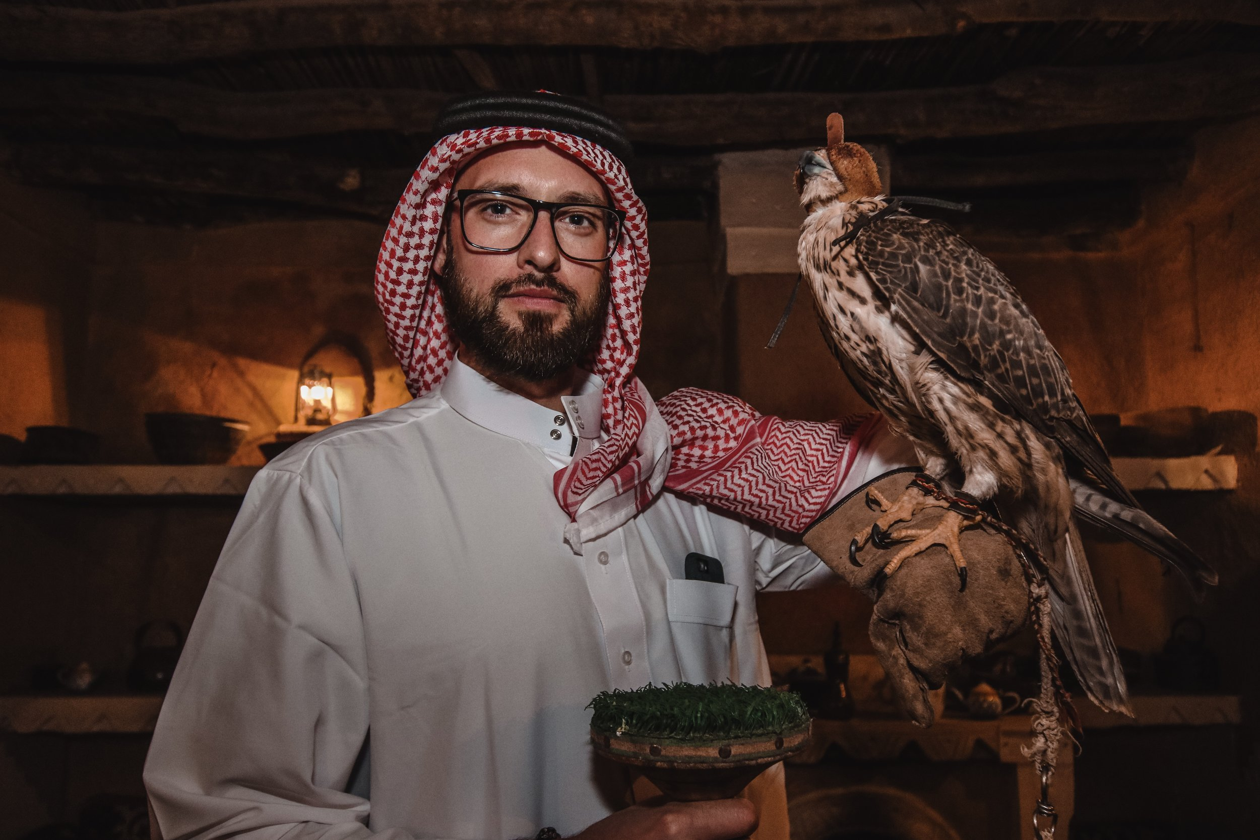Tristan wearing his traditional thobe holding the resident hawk at Nadj Village.