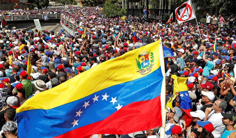 A Venezuelan flag waves as opposition supporters take part in a rally against President Nicolas Maduro's government in Caracas, Venezuela, January 23, 2019. (Carlos Garcia Rawlins/Reuters)