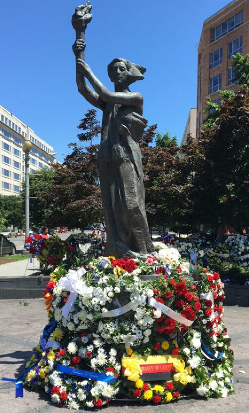 Wreaths and bouquets adorn the foot of the VOC Memorial statue following the ceremony.