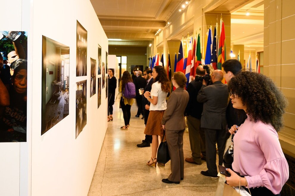 "Opening reception attendees view the ""Victims of Venezuela's Dictatorship"" photo exhibition at the OAS on Monday, July 8."