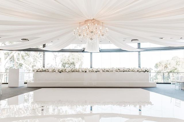 White gloss dance floor, bridal table, staging, lectern cover and DJ booth for @blondeandbluestyling  Coordination & Styling  Decal @hartleydesign  Florist @matthewlanders  Draping & Chandelier @eventstyleperth  Chairs @hiresociety  Stationary @laladesignperth  DJ @steven_patino  Venue @fraserseventsweddings  Cake @delarosacakes