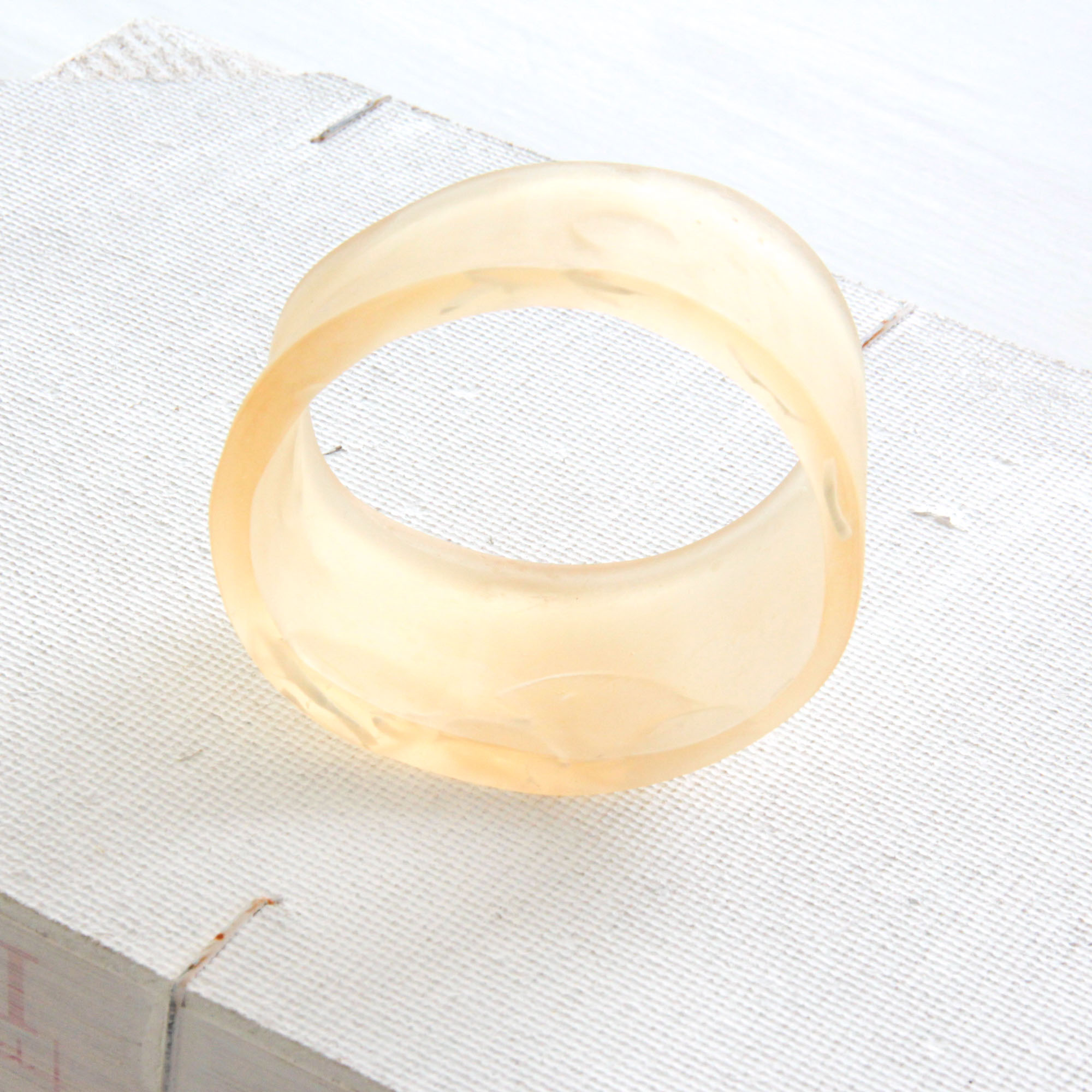 nude resin bangle - • handcasted• transparent nude colour with white inlays• bold, chunky and chic• br445 euro