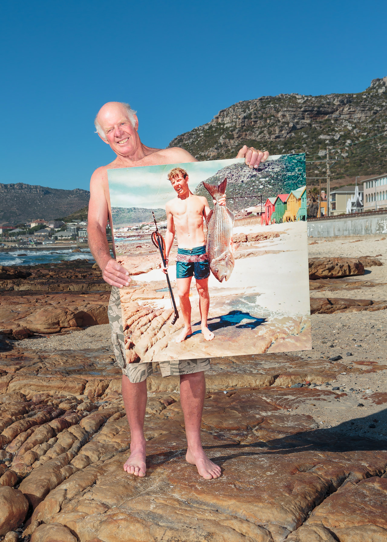 South African Geoff Fridgeon poses with a picture of himself in the same spot 46 years ago holding a musselcracker seabream—a species near threatened with extinction today