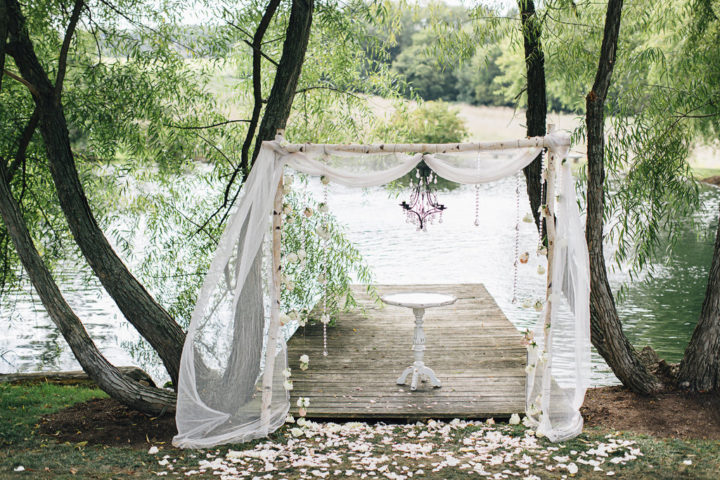 Loved this wedding ceremony arbor with hanging chandelier, crystals, and flowing fabric!