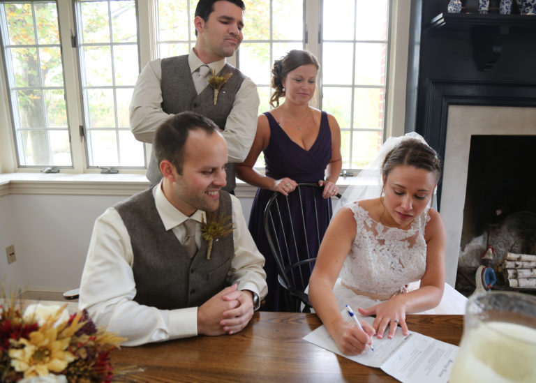 Erika and Matt decided to do a self uniting marriage ceremony. Here they are signing their marriage license with their two witnesses. Photo by A Reflection by Sherry