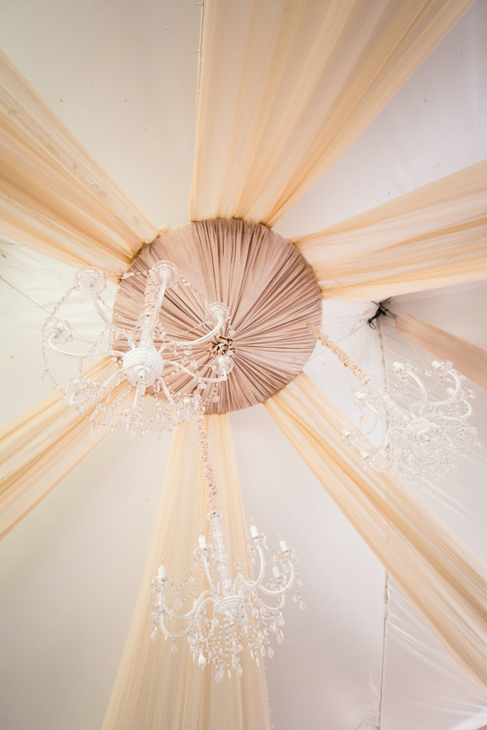 The couple added fabric draped throughout the tent with lights in them as well as chandeliers hanging from the tent ceiling.