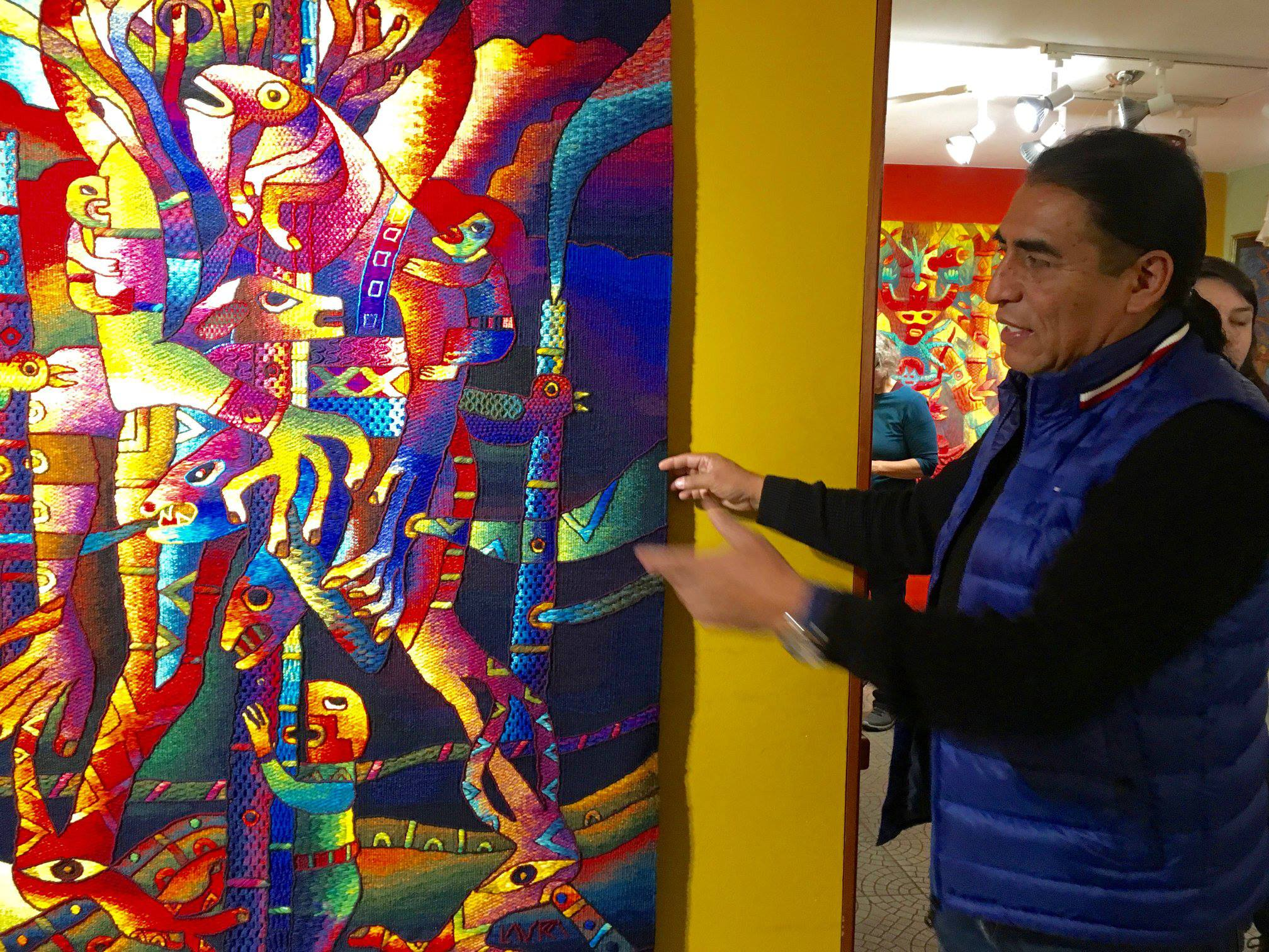 Maximo showing several of his techniques on a finished tapestry.