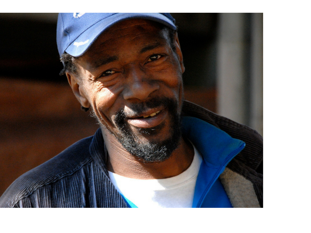 "TJ - TJ lived in a house in San Francisco for 40 years before becoming homeless, but now he can't imagine living anywhere other than his dwelling under a freeway that he now calls home. ""I didn't shed a tear when I left my house, but I'll be devastated when I have to leave here,"" he says. He loves meeting all the people who pass through his area, including the SOS outreach team. ""Even though people say we're homeless,"" he says, ""we get more house calls out here than anyone."" (Photo credit: Marlena Hartman-Filson)"