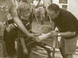 Chris Harris, of Philip Koomen Furniture, showing a youngster how to spoke shave.