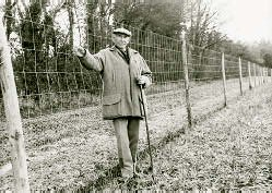 Walter stands beside his deer and rabbit proof fence.