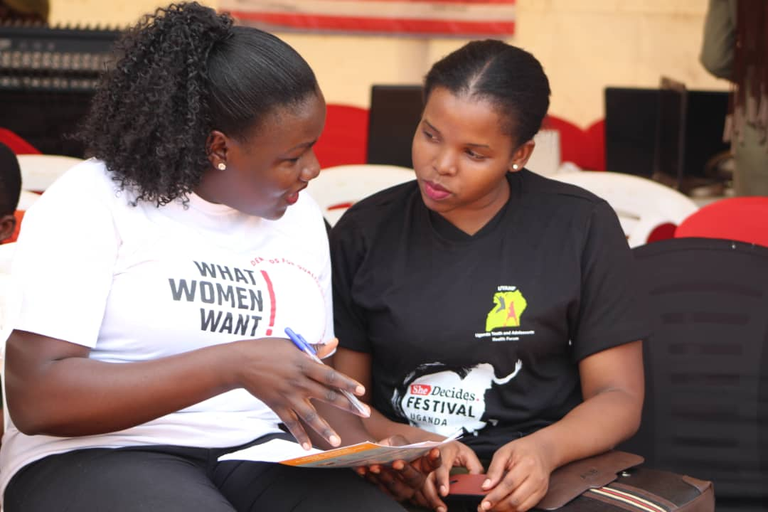 Mobilization_Uganda_WRA Uganda citizen journalist Winfred Ongom engages a woman wbout WWW at the She Decides Festival Kampala.jpg