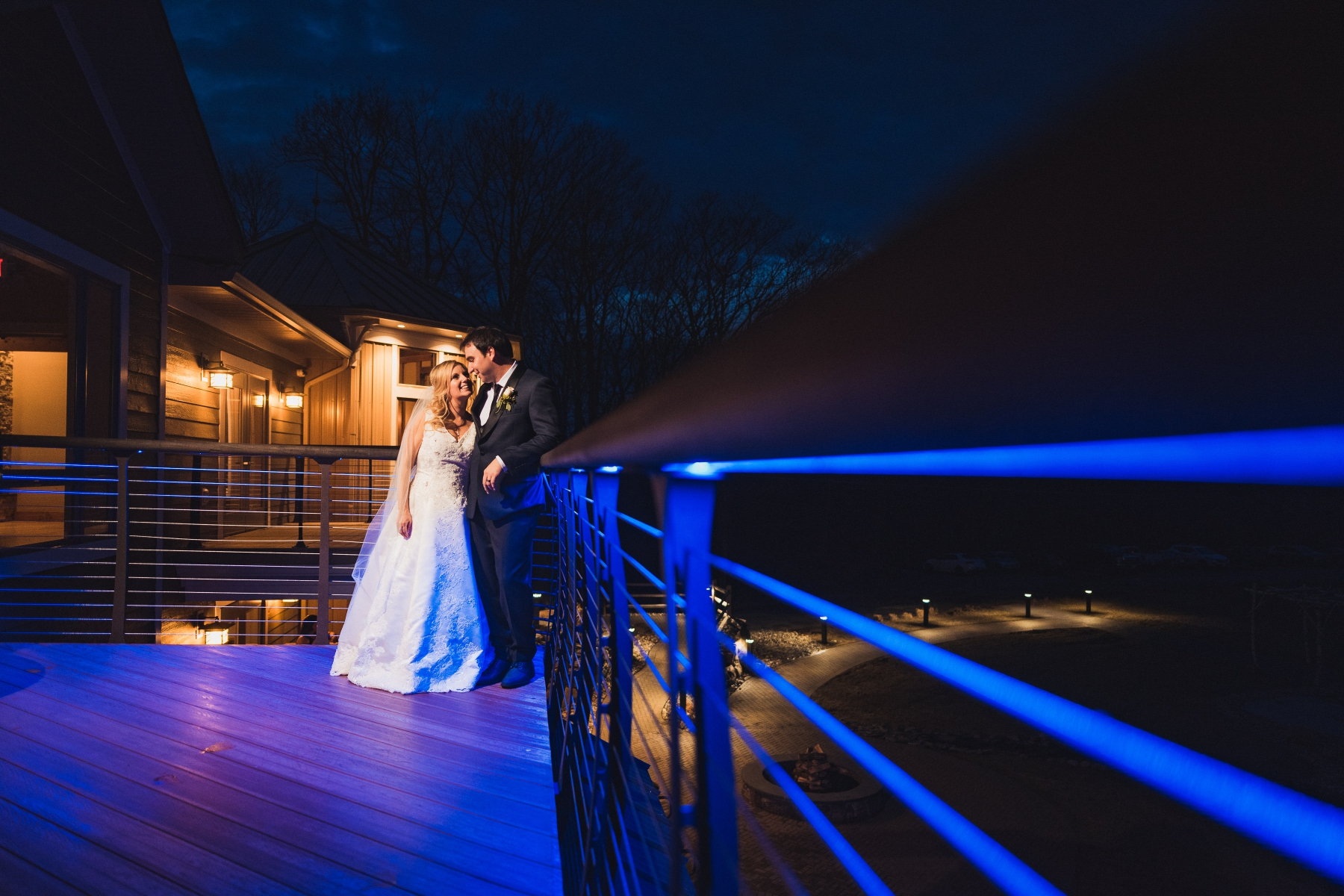 Nearing the end of the night, i wanted to do one more night portrait of the two of them. Rock Island Lake Club has this really cool blue uplighting that they use on the patio, so i took them outside, incorporated them as leading lines into my image of the two of them, right before they're going to be announced as husband and wife.