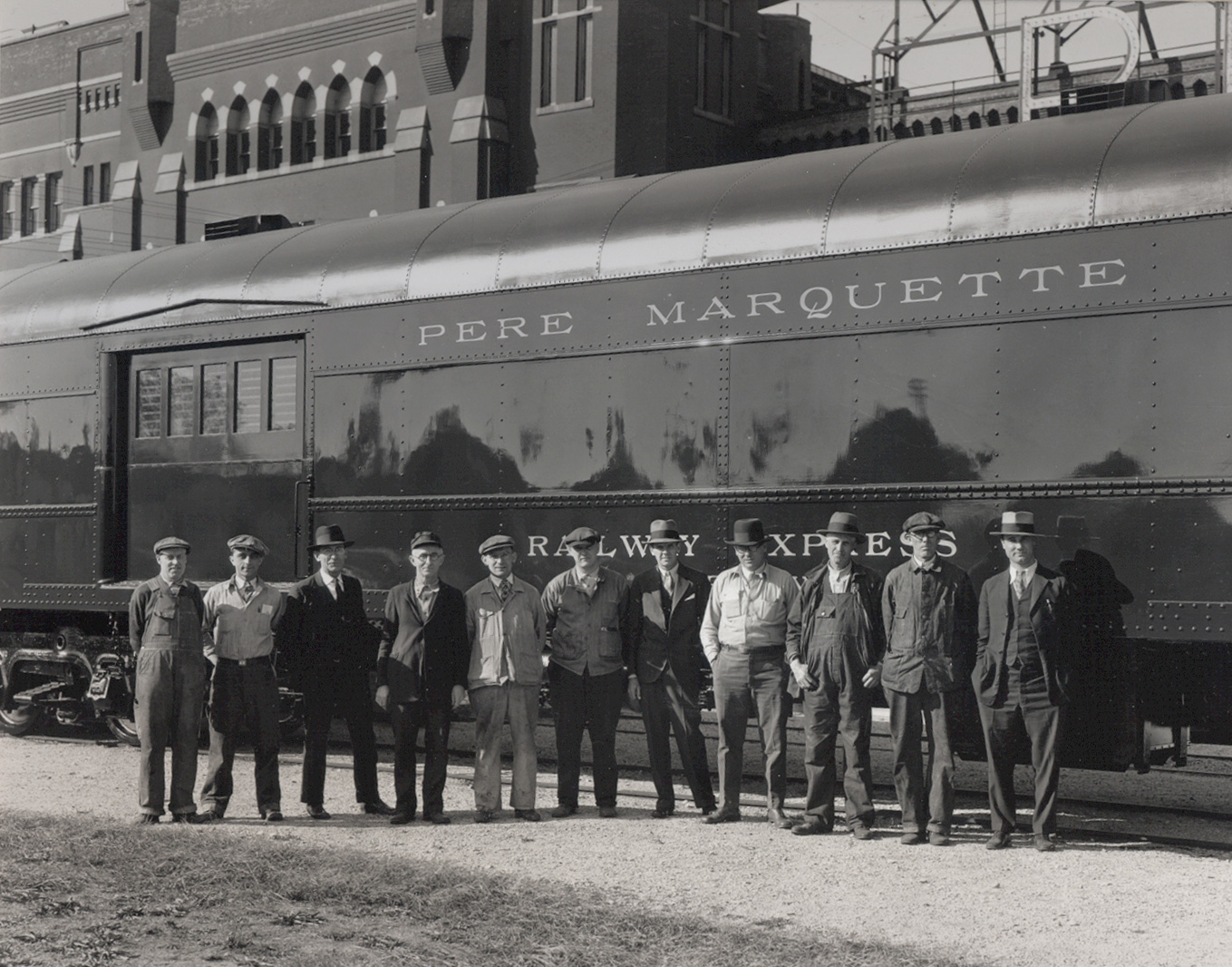 """This photo is believed to be taken right after an inspection of a rail car ordered by the Pere Marquette rail line. The men pictured were likely foremen involved in its production. The man on the right is believed to be a representative of the rail line. He likely made a visit to the fourth floor of the 300 building, which was called the """"booze floor"""" to sip whiskey before inspecting the car and taking delivery."""