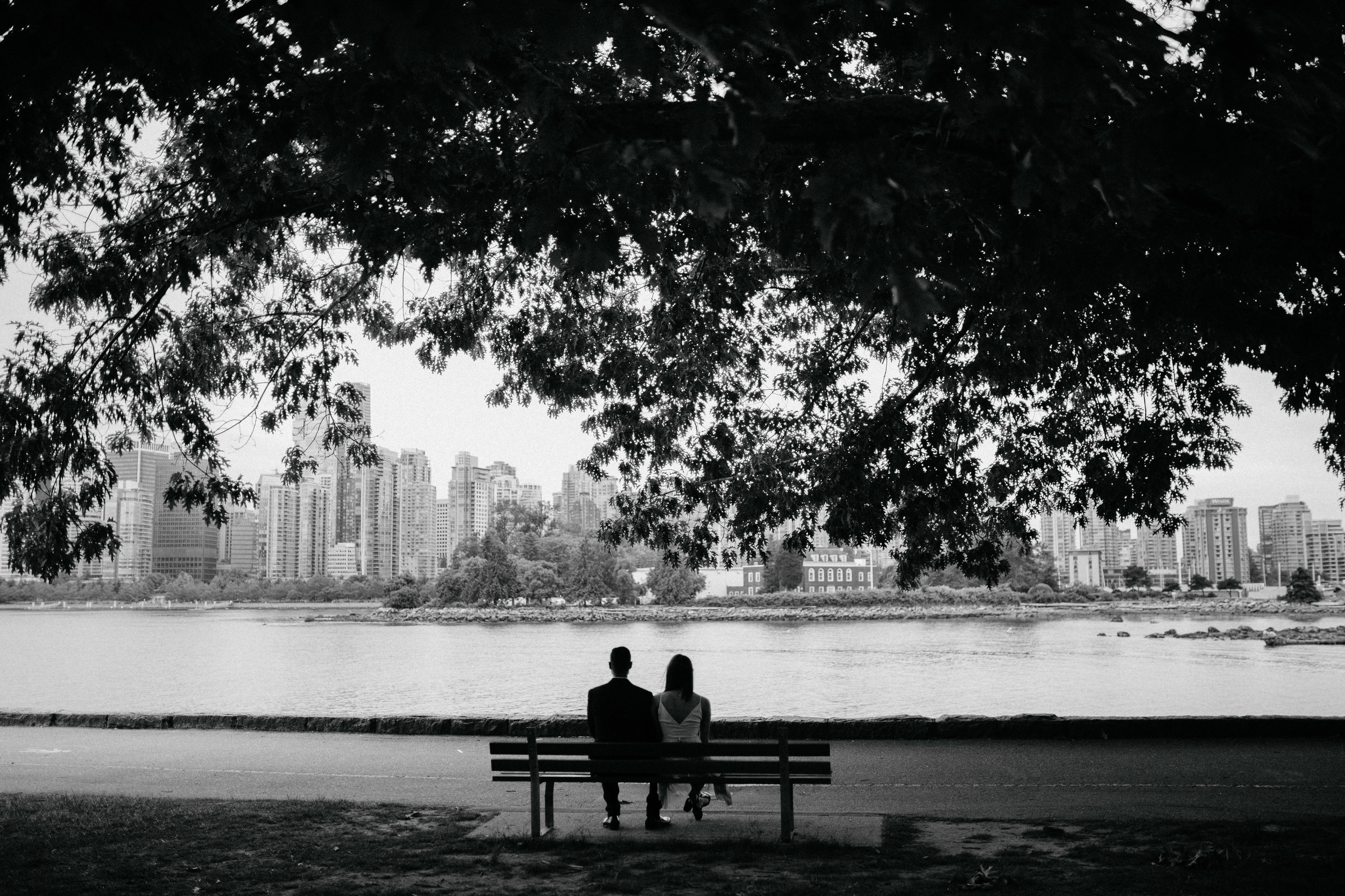 Engaged couple sitting on a bench by the seawall at Stanley Park, while looking at the view of coal harbour.